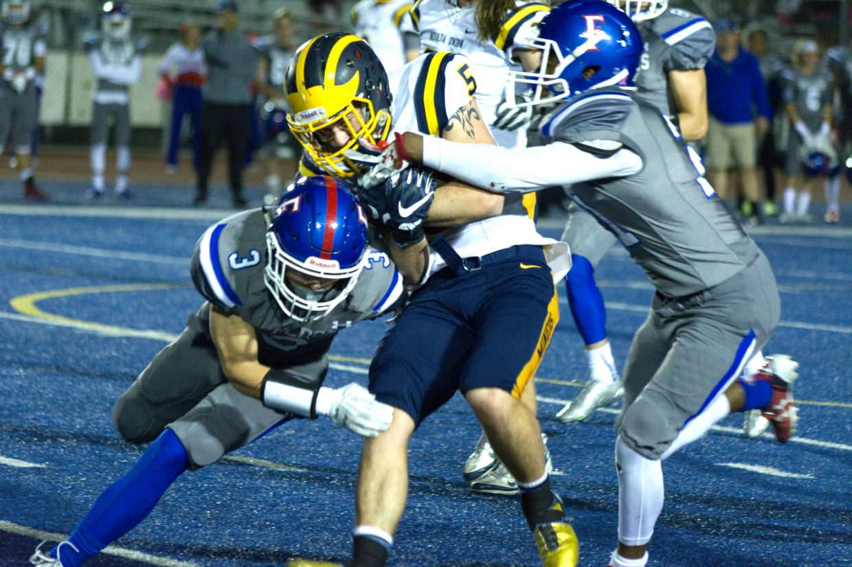 Nevada Union's Tyler Nielson is tackled by a pair of Folsom defenders.