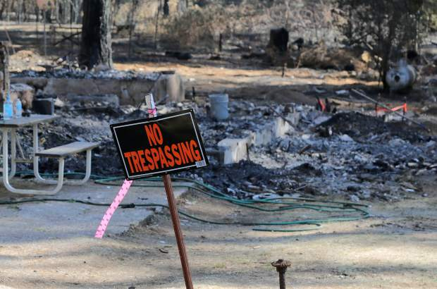 The remnants of a home sit behind a no trespassing sign on McCourtney Road after the McCourtney Fire swept through the area more than a week ago causing significant structure loss.
