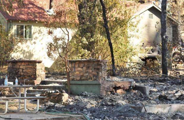 A rock foundation is all that remains of a home on McCourtney Road while the home in the background received some fire damage but will still be inhabitable.