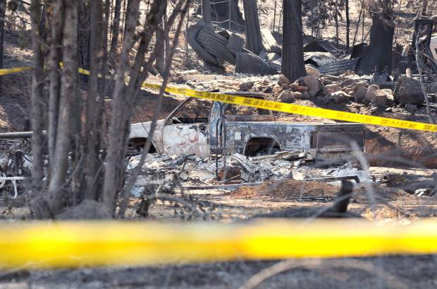 Crime scene tape surrounds the charred remnants of a property along McCourtney Road after the McCourtney Fire swept through here late Saturday October 7th. The fire was 100 percent contained within a week.
