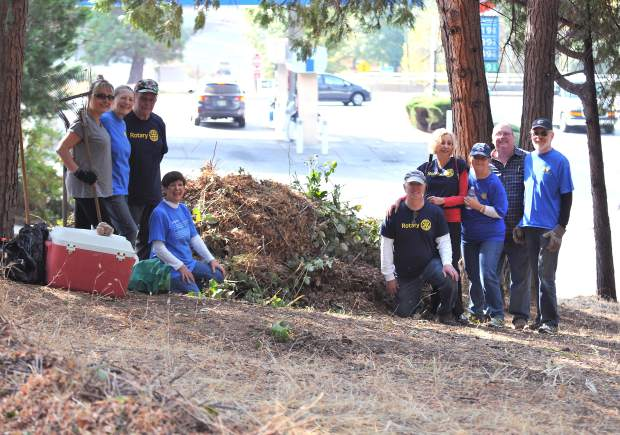 Members of the Nevada City Rotary Club stand next to one of the large piles of weeds and blackberry bushes they cut down at Penzance Park in Nevada City, located at the corner of Sacramento and Prospect Streets. The park was commemorated in the 1980s following the designation of Penzance in Cornwall England as Nevada City's sister city.