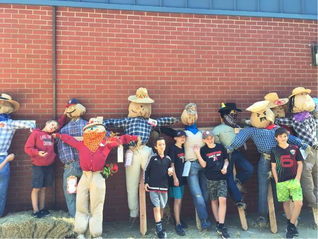 Students from Deer Creek School in Ms. Bairs fifth grade class pose with the scarecrows they made to raise money for Heifer International. Scarecrows are on sale at Prospector's Nursery and all the funds go to help families in need.
