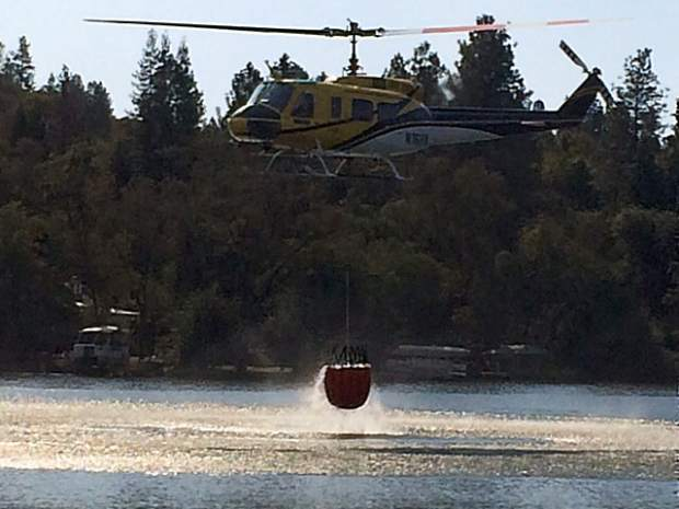 Helicopter taking water from Lake Wildwood to battle the Lobo Fire.