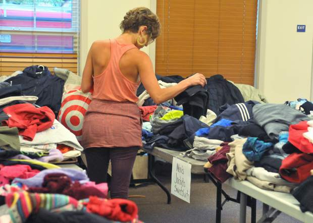 An evacuee from the Santa Rosa fires, staying in Nevada County with friends, picks through items donated to the Rough and Ready Fire Department Tuesday evening. Though her home was saved, she still was without goods as evacuation orders had not yet been lifted in her neighborhood.