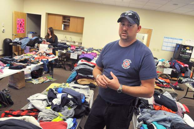 Rough and Ready Fire Captain Tim Pettee stands in the Rough and Ready Fire Department's auxiliary room that has been filled with sorted clothing items. Pettee explains that these items are from the first day's worth of donations alone. Many other bags of donations have yet to be sorted.