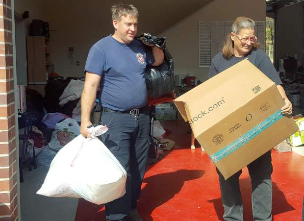 Rough and Ready Fire Capt. Matt Wright and volunteer Teresa Glasscock, who serves as treasurer for the department's Behind the Scenes group, load donated goods onto a truck for distribution to fire victims Tuesday.