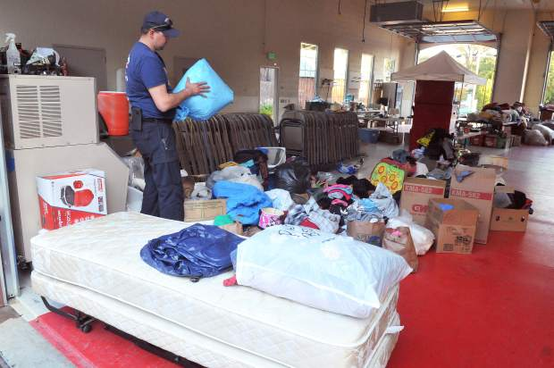 Rough and Ready Fire Captain Tim Pettee sifts through the hundreds of donations that have been brought to the fire station following the wildfires that swept through Northern California.
