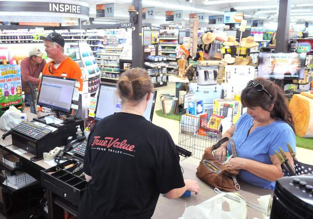 Penn Valley True Value Hardware employee Trenidy Dickinson helps customers from behind the register. The hardware store is one of the larger tax revenue generators in the county.