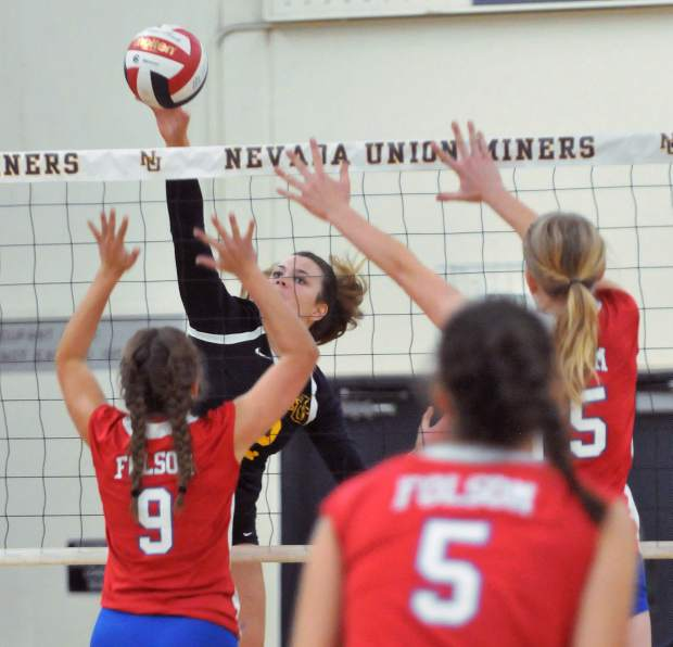 Nevada Union's Meadow Aragon spikes the ball over the net in the face of a slew of Folsom defenders during the Miners win in three sets over the visiting Bulldogs.