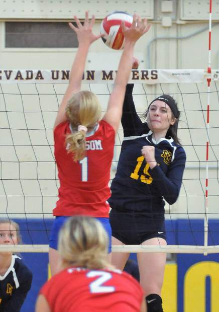 Nevada Union senior Danica Minard (15) spikes the ball past Folsom's Samantha Bigly (1) during the Miners' Wednesday night win in three sets over the visiting Bulldogs.
