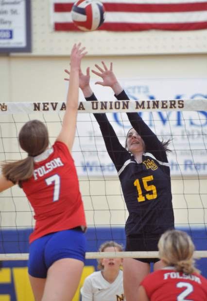 Nevada Union senior Danica Minard tries to block a lobbed ball from Folsom's Sydney Radell (7) during the Miner's win in three sets over the visiting Bulldogs.
