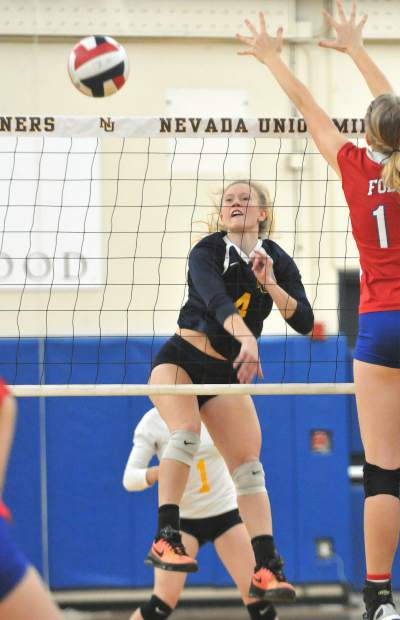 Nevada Union's Regan Heppe (4) spikes the ball past a Bulldog defender during the Miners sweep of Folsom in three sets Wednesday at Albert Ali Gymnasium in Grass Valley.