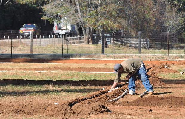 A farmer installs piping on a ranch in the 16000 block of Highway 174 on Tuesday. Current Caltrans plans call for widening the highway through this section, which some homeowners say makes putting any time or money into property improvements a risky move.