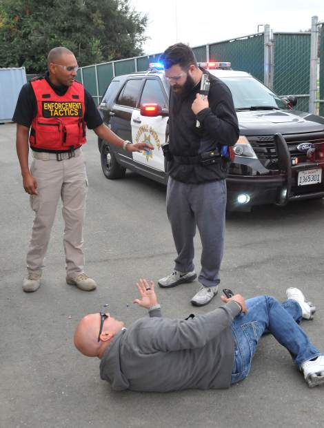 Enforcement Tactics Unit officer Ukau Dungca gives media boot camp cadet Frankie Tovar insight into his simulation during last week's CHP media boot camp held at the CHP's West Sacramento training academy.