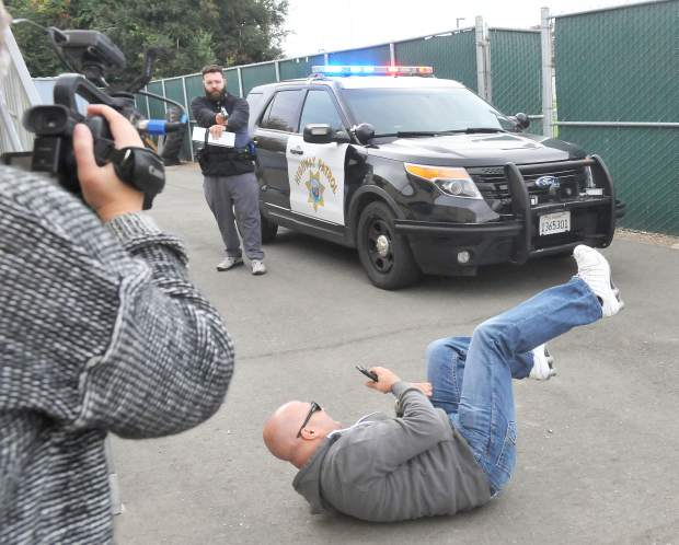 A roleplaying traffic stop suspect rolls on the ground after being shot by media boot camp cadet Frankie Tovar with Simunitions ammunition.