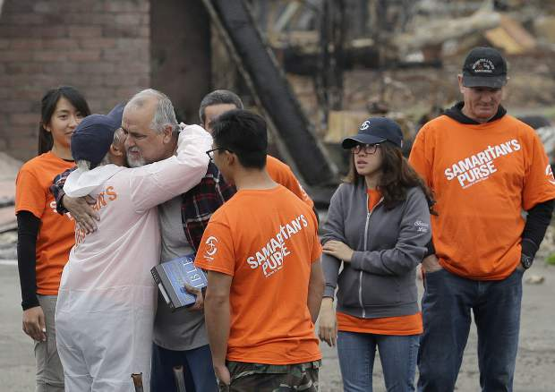 Larry Keyser, third from left, hugs volunteers from Samaritan's Purse disaster relief after they helped him sift through remains of his family's home destroyed by fires in the Coffey Park area of Santa Rosa, Calif., Wednesday, Nov. 8, 2017. Rumbling front loaders began scraping up the ash and rubble of nearly 9,000 destroyed homes and other structures in Northern California this week as the U.S. Army Corps of Engineers launched a new phase of the largest wildfire clean-up in the state's history. (AP Photo/Jeff Chiu)