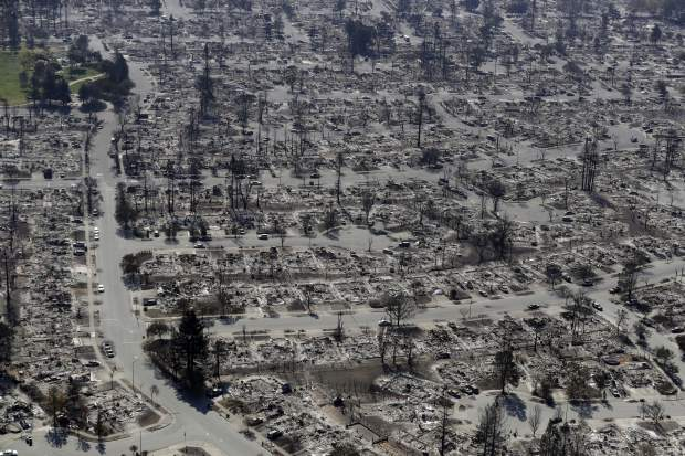 FILE - In this Oct. 14, 2017, file photo, an aerial view shows the devastation of the Coffey Park neighborhood after a wildfire swept through in Santa Rosa, Calif. Rumbling bulldozers have started scraping up the ash, charred wood and crumbled bricks left from thousands of homes and buildings destroyed by wildfires in California wine country. U.S. Army Corps of Engineers contractors began the work this week in flattened, blackened blocks of Santa Rosa's Coffey Park neighborhood. (AP Photo/Marcio Jose Sanchez, File)