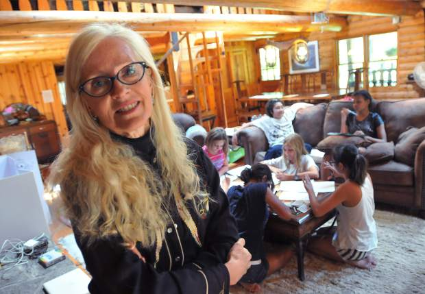 Education convener for the Climate Change Agents Camp, Teresa Langness, stands in the cabin where campers work on a project in advance of their performance at the Nevada City Farmer's Market.