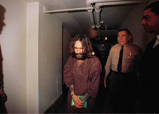FILE - In this 1969 file photo, Charles Manson is escorted to court in Los Angeles during an arraignment phase. Authorities say Manson, cult leader and mastermind behind 1969 deaths of actress Sharon Tate and several others, died on Sunday, Nov. 19, 2017. He was 83. (AP Photo, File)