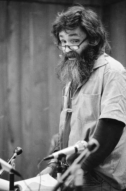 FILE - In this Feb. 4, 1986, file photo, convicted mass murder Charles Manson reads a rambling statement at his parole hearing in San Quentin, Calif. Manson, who is serving life in prison for the murder of actress Sharon Tate and five others, said he would go to Libya, Iran, South America or France if released. Authorities say Manson, cult leader and mastermind behind 1969 deaths of Tate and several others, died on Sunday, Nov. 19, 2017. He was 83. (AP Photo/Eric Risberg, File)
