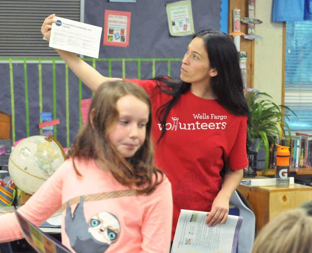 Rocklin Wells Fargo associate Vanessa Ray works with a group of second graders during Thursday morning's junior achievement program at Chicago Park Elementary School.