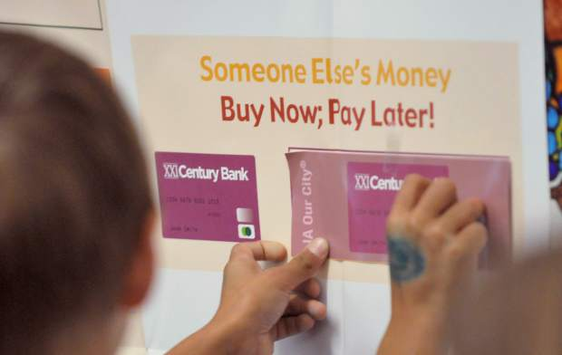 Students place the different forms of payment onto a board describing what each form of payment does. Students learned about checks, debit cards, credit cards, money orders, and electronic payment.