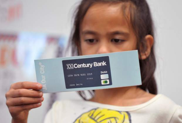Chicago Park Elementary third grader Arriani Cope reads information on the back of a mock debit card being used as an educational tool at Chicago Park Elementary School's junior achievement program.