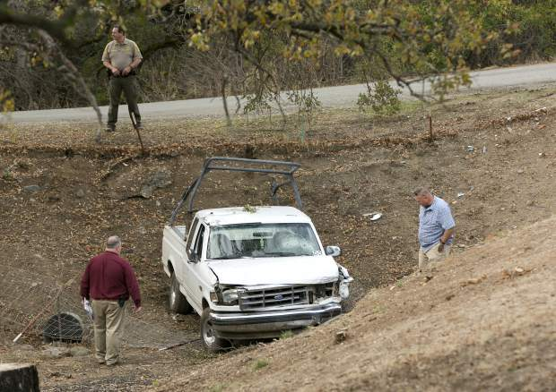 Investigators view a pickup truck involved in a deadly shooting rampage at the Rancho Tehama Reserve, near Corning, Calif., Tuesday, Nov. 14, 2017. A gunman driving stolen vehicles and choosing his targets at random opened fire