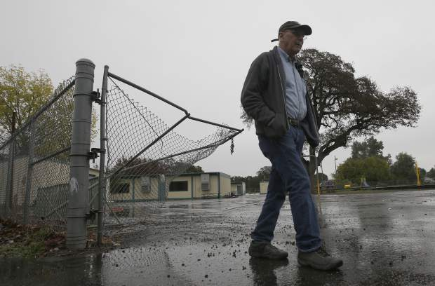 Randy Morehouse, the maintenance and operations supervisor for the Corning Elementary School District, walks past the gate, at the Rancho Tehama Elementary School, Wednesday, Nov. 15, 2017, that gunman Kevin Janson Neal crashed through during his shooting rampage at Rancho Tehama Reserve, Calif., Tuesday. Neal killed five people, including his wife before being shoot and killed by Tehama County Sheriff's deputies. Neal is believed to have spent six minutes shooting into the school before driving off to continue his shooting spree. One student was shot but is expected to survive. (AP Photo/Rich Pedroncelli)