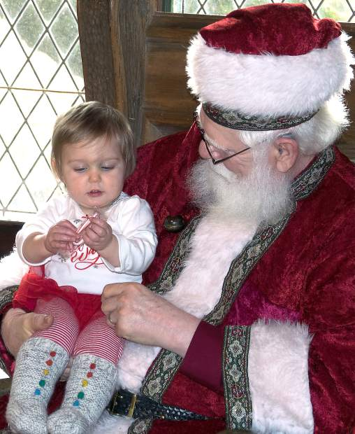 Emma Lou Brewer, 1, takes a seat with Santa Saturday morning at Holidays at Empire Mine.