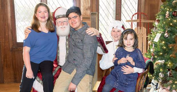 Photo by John Hart Mikayla Kauinana, 16, and Justin Kauinana, 14, take a seat on Santa's lap while sister Kendyl Kauinana, 6, sits with Mrs. Claus Saturday morning during Holidays at Empire Mine. t