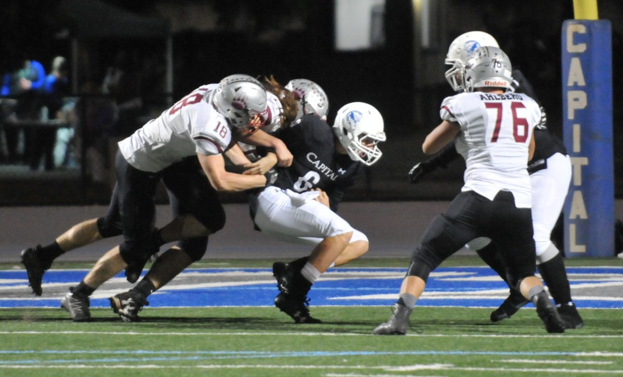 A slew of Bear River defenders take down Capital Christian quarterback Jake Cruz (6) in the backfield during the Bruins' first round Division V playoff win over the Cougars Thursday night in Sacramento.