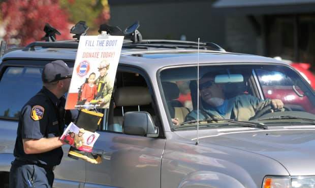 Cal Fire's Rich Wilson accepts a donation from a passing driver on Sutton Road Saturday morning. At least oncea a year, local Cal Fire firefighters help fundraise for the Muscular Dystrophy Assocaition to help children experience things they otherwise wouldn't.