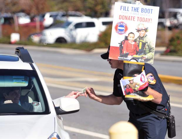 Cal Fire's Rich Wilson, an Engineer from the Loma Rica station, collects a donation from a passing driver at the Brunswick and Sutton intersection Saturday.