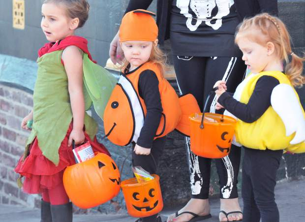 A trio of safe trick or treaters pause to see what each other has in their halloween treat baskets.