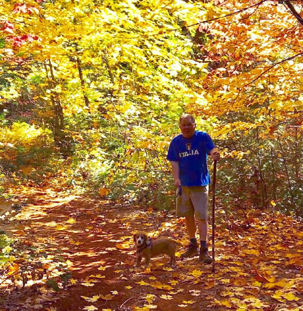 A local resident admiring the fall leaves with his dog.