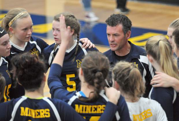 Lady Miners head coach Chrys Dudek talks to his team in between sets during Tuesday's playoff game.