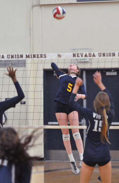 Nevada Union's Faith Menary pulls back to spike the ball over the net during the Lady Miners' win in three sets over the visiting Vista Del Lago High School Eagles.