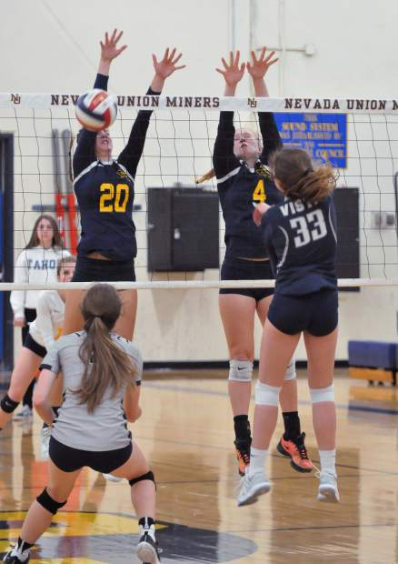 Nevada Union's Greta Kramer (20) gets the block for the Lady Miners, helping to win the second of three sets against Vista Del Lago High School during the first round of the playoffs Tuesday night.