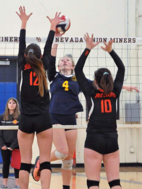 Nevada Union's Regan Heppe (4) hits between two Vacaville players during a playoff game Thursday. Heppe finished with 31 kills to lead NU.