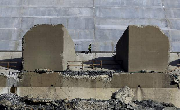 A worker walks along the lower end of the Oroville Dam spillway, Thursday, Nov. 30, 2017, in Oroville, Calif. California water officials and the construction manager said Thursday, that recently found hairline cracks on the spillway are normal and expected in reinforced concrete because it shrinks as it cures. (AP Photo/Rich Pedroncelli)