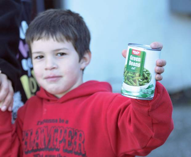 Hunter Webb, 5, holds his can of food proudly before dropping the donation off at Grass Valley Charter School Thursday morning for Donation Day, a 125-year-old tradition of giving in Grass Valley.