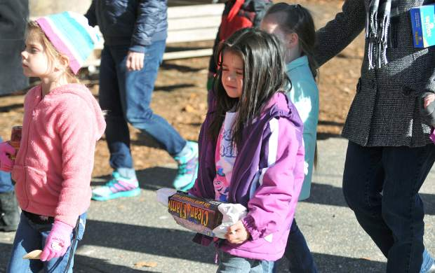 A youngster hauls in a compressed fire log during Thursday's Donation Day.