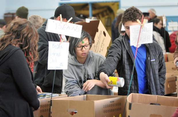 Grass Valley Charter School's Lian Trowbridge (center) helps sort the thousands of donated canned goods Thursday morning along with a group of other school volunteers.