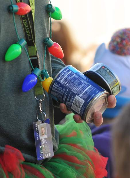 A Deer Creek Elementary School faculty member carries a handful of canned goods towards Grass Valley Charter School during Thursday's Donation Day parade.