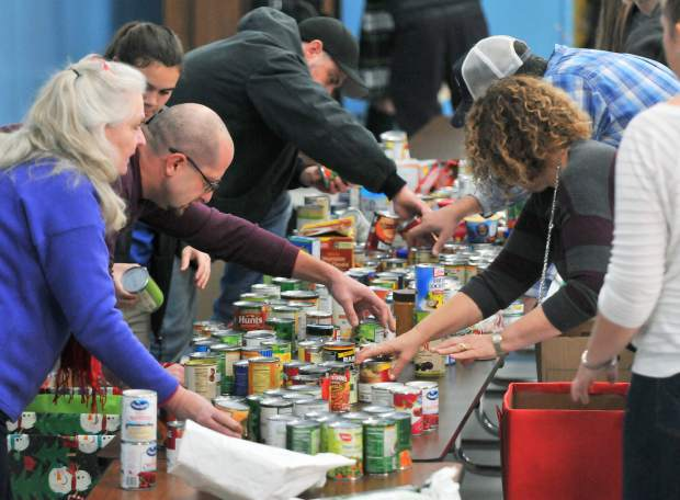 Volunteers from the Ladies Relief Society, FFA, Nevada County Probation Dept. and Grass Valley Charter School work to quickly sort the thousands of donated food items Thursday inside the multi purpose room at Grass Valley Charter.