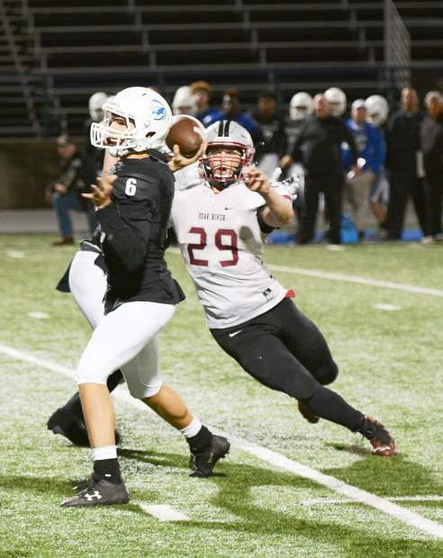 Bear River's Austin Baze closes in on Capital Christian's quarterback during a playoff game.