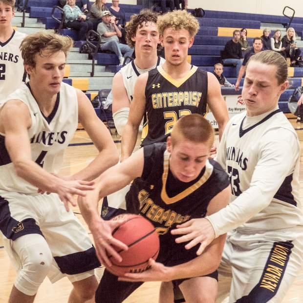 Nevada Union's Jack Fraser and Justin Houlihan converge on a Enterprise player during the first round of the Nevada Union Invitational Tournament Thursday. The Miners topped Enterprise, 51-49.