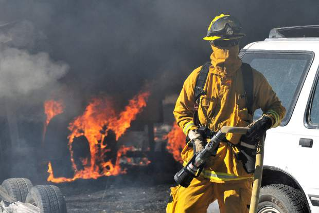 A firefighter readies to place water on a portion of the Pleasant Fire burning in North San Juan Wednesday afternoon.
