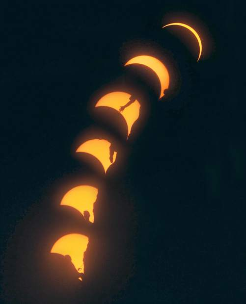 A rock climber is silhouetted by the solar eclipse while climbing Monkey Face in Smith Rock State Park in Terrebonne Oregon August 21.